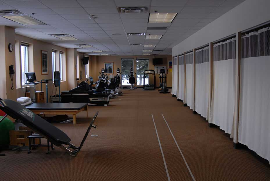 the south gym is a long room with windows on one side, exercise equipment, and curtains to separate out private rooms
